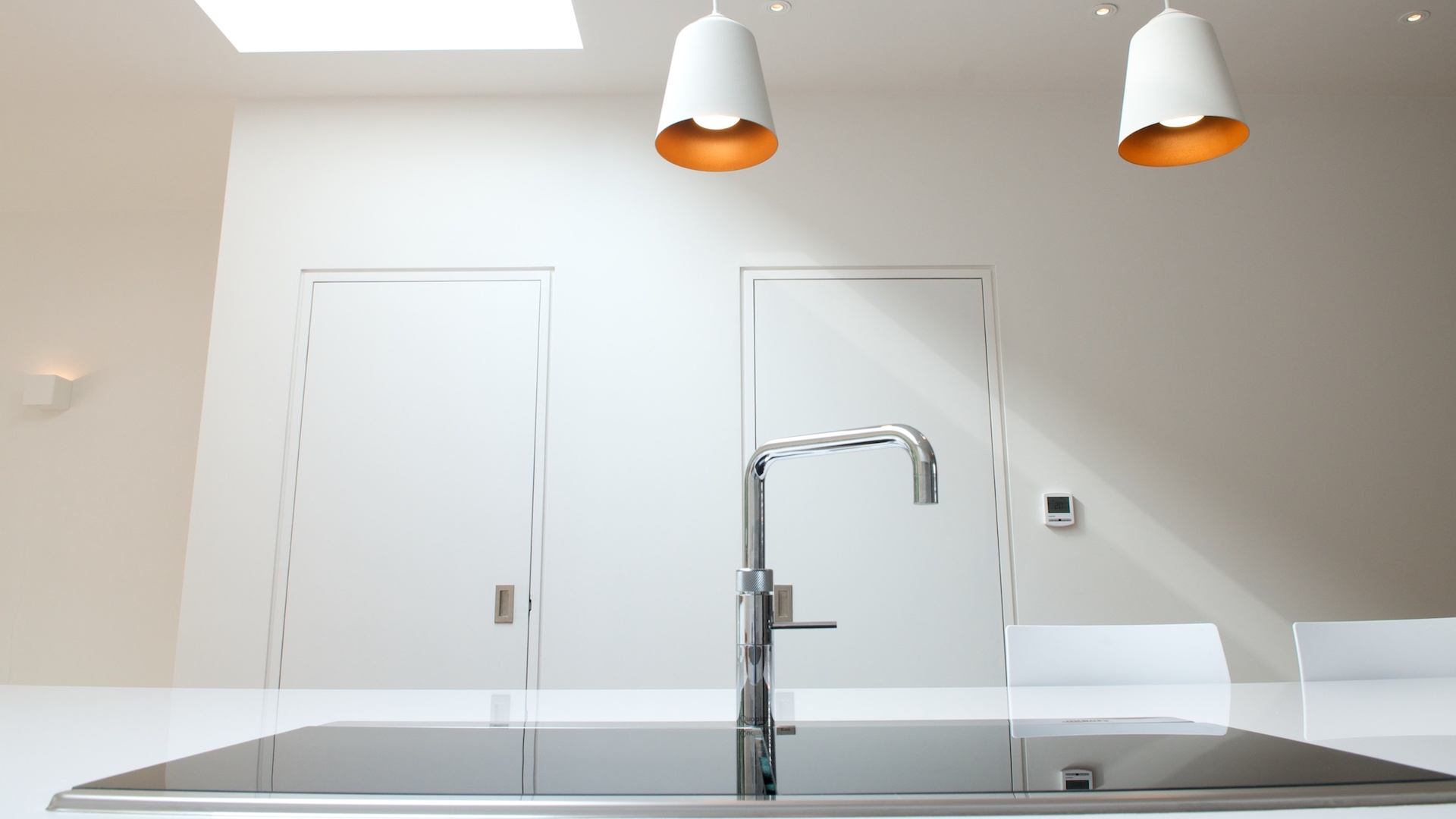 Modern sink with tap and lights above with orange detail inside.