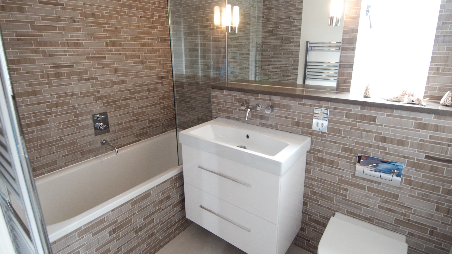 White bathroom sink with white bath and light brown narrow tiles.