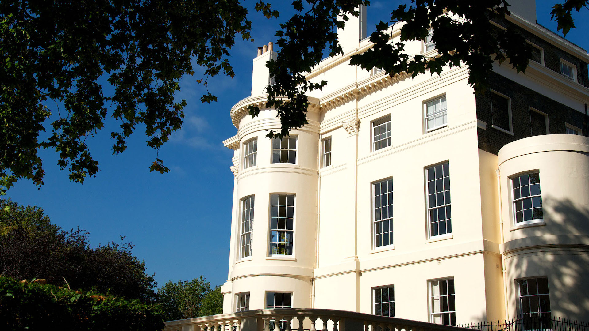Regency building in West London, with image taken from ground looking up with beautiful clear blue sky in background.