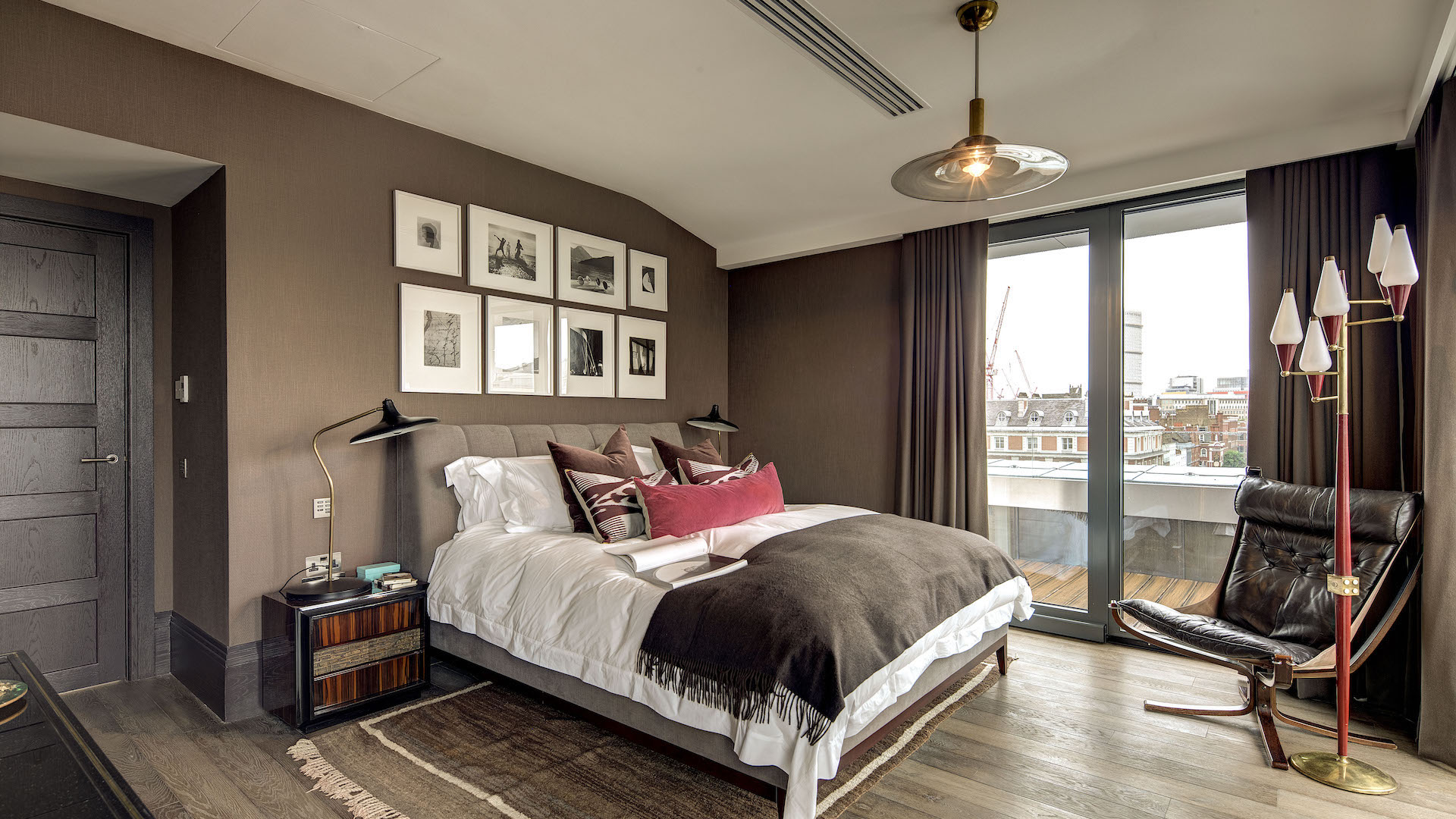 Modern bedroom with classic brown furniture in penthouse apartment in London