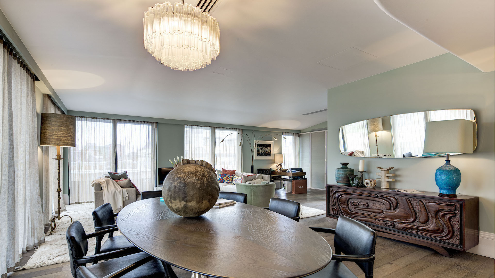 Open plan living room with oval dining table, with mint coloured walls, classic furniture with beautiful and contemporary chandelier.