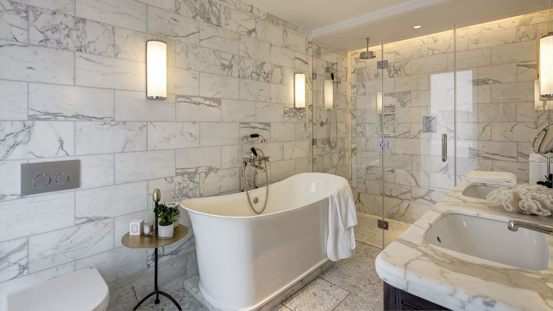 Beautiful white marble bathroom with deep, luxurious bathtub with walk-in shower in the corner.