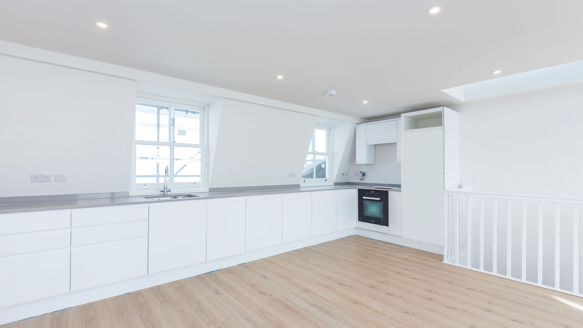 Large galley kitchen with crisp white cabinets, sink, oven and room for a fridge