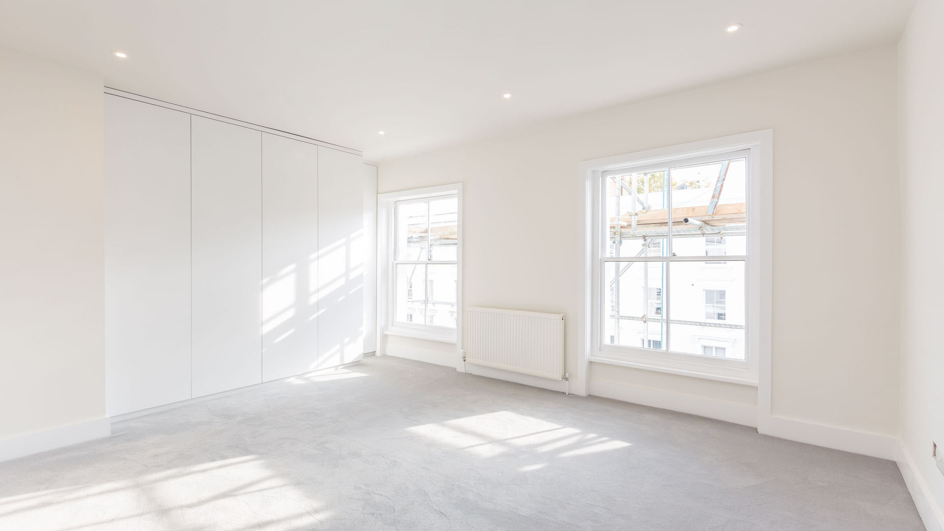 Large living room with light grey carpet, with light flooding in through large, sash windows.